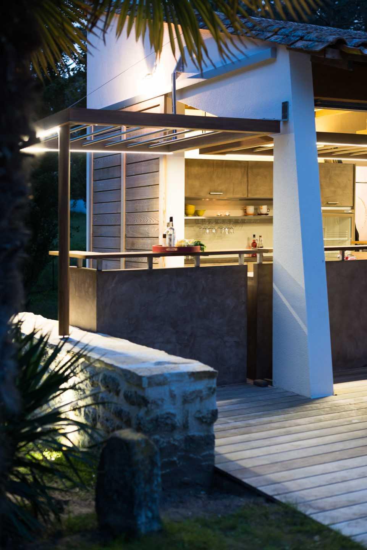 Bar vu depuis la piscine Eclairages Leds intégrés aux faux plafonds et plan de travail en céramique par Frédérique Bargeas