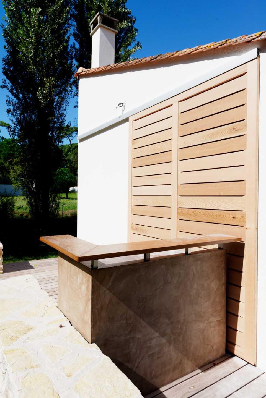 Porte coulissante permettant de fermer la cuisine pendant l'hiver Eclairages Leds intégrés aux faux plafonds et plan de travail en céramique par Frédérique Bargeas
